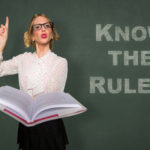 Teacher holds rule book know the rules message classroom lecture